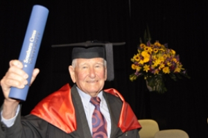 Photo of man holding university degree, he has a mortar board on his head and a gown with red collar who has engaged in lifelong learning.