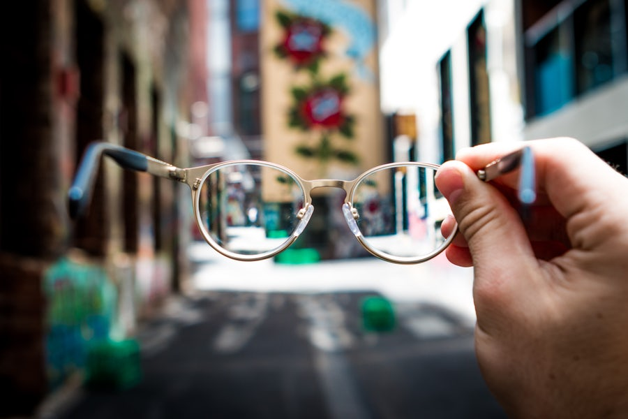Person holding glasses in a laneway to a lifelong learning centre.