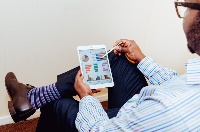 Man in blue shirt and purple socks sitting with ipad looking at charts