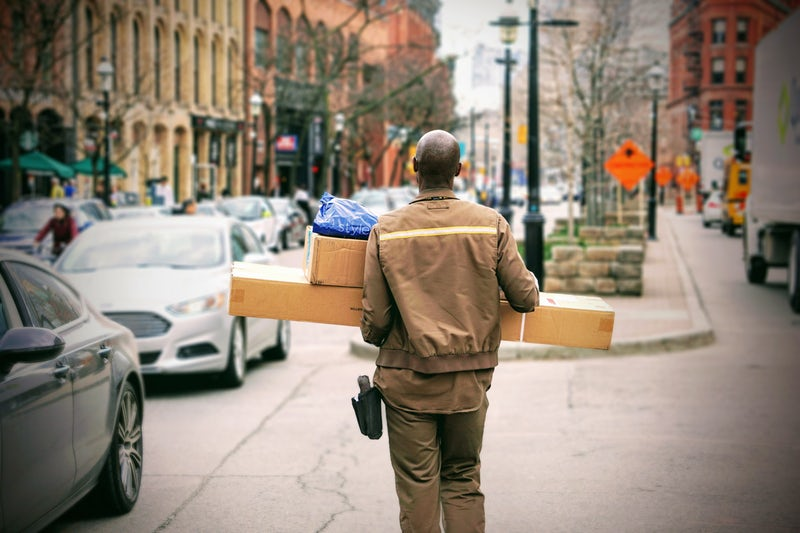 Man wearing yellow jacket and pants carrying packages in a city street