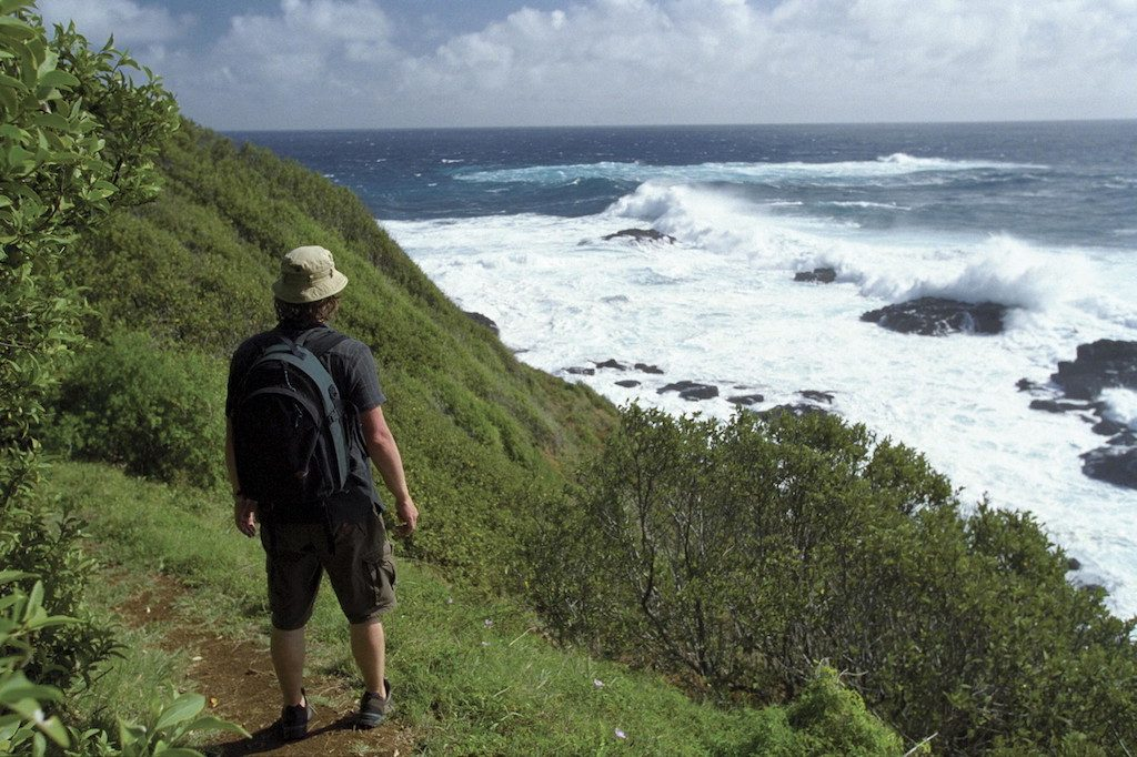 man hiking along track by ocean