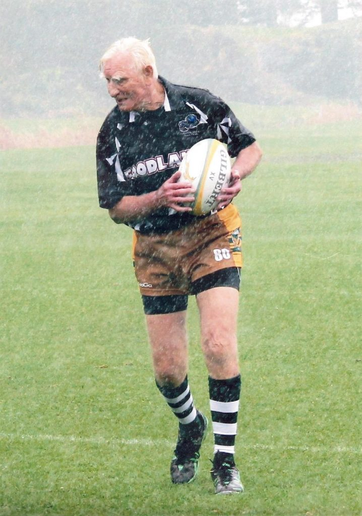 Ian Anderson with rugby ball in rain on green field