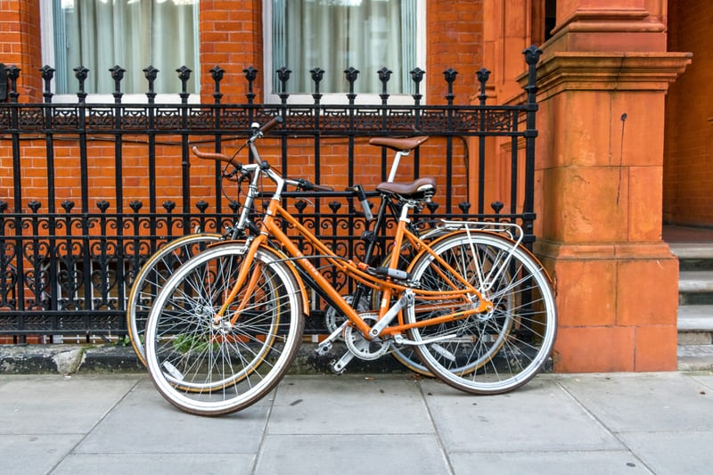 Orange bicycles leaning against a wrought iron fence of a London home owned by people thriving in retirement