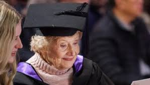 older lady with mortar board on head, wearing academic gown an pink jumper