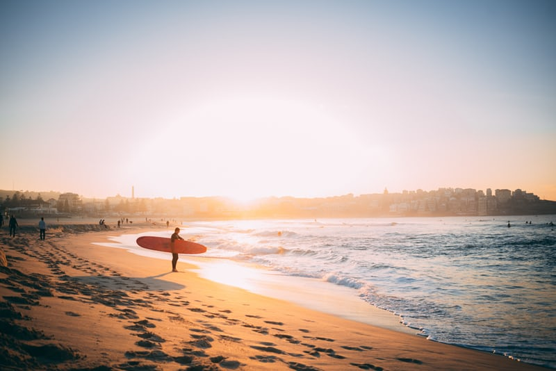 surfer standing on beach with surfboard about to go into ocean