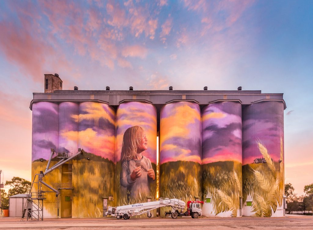 Painted silos with a crane on a truck in front of it.