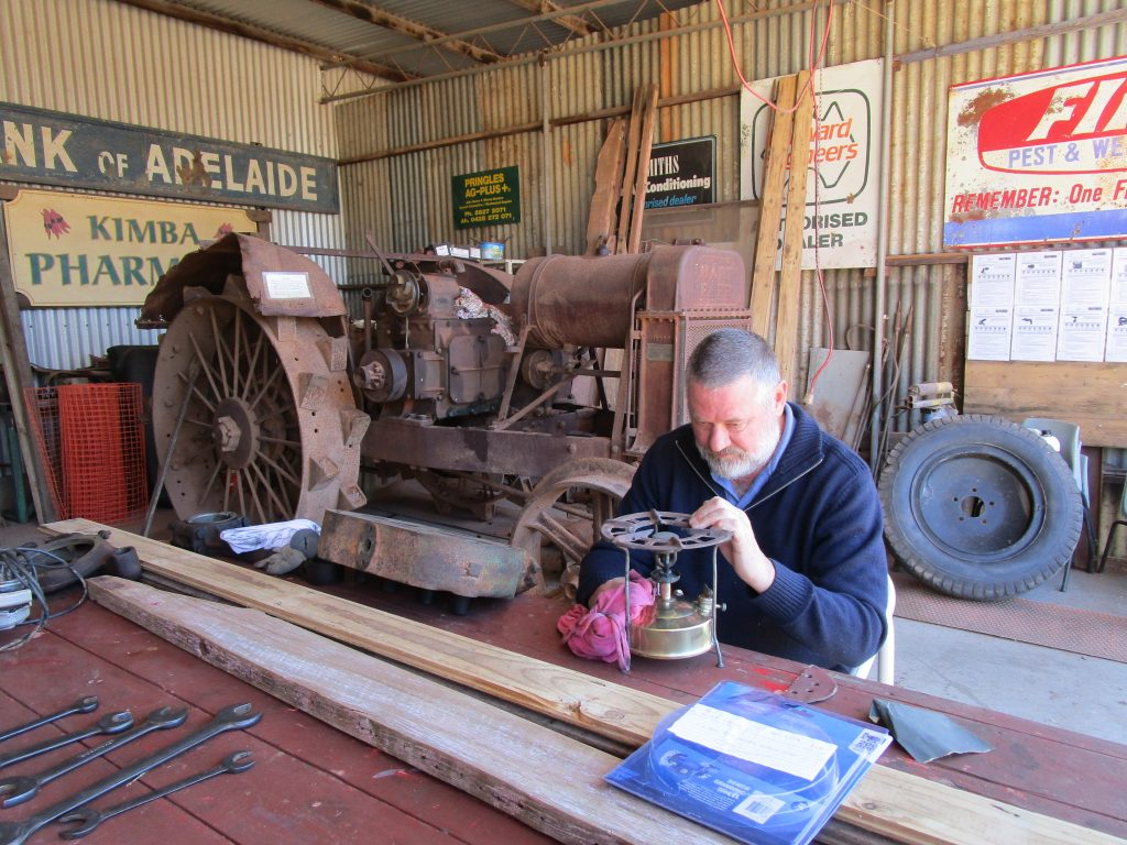 Man sitting down at a table working in a shed with an old tractor behind him.