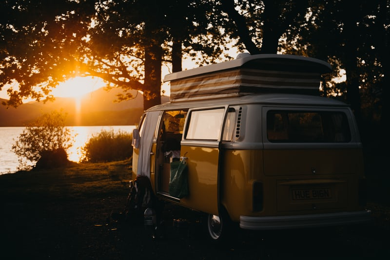 Mustard coloured Kombi van beside a lake