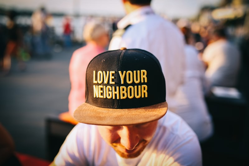 Man with cap on and love your neighbour written on cap