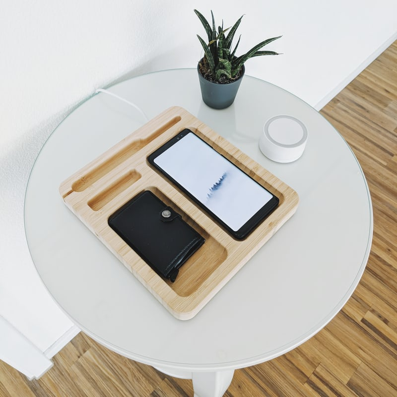 Mobile phone on small white table with plant pot next to it.