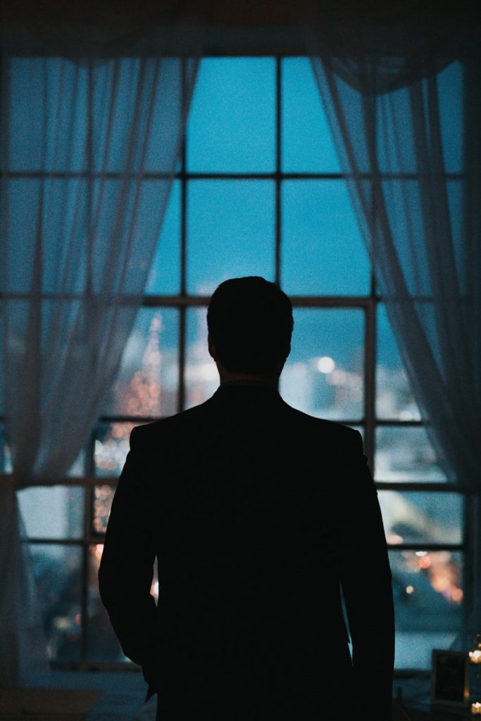 man standing at window, silhouette showing, the life of a spy in retirement