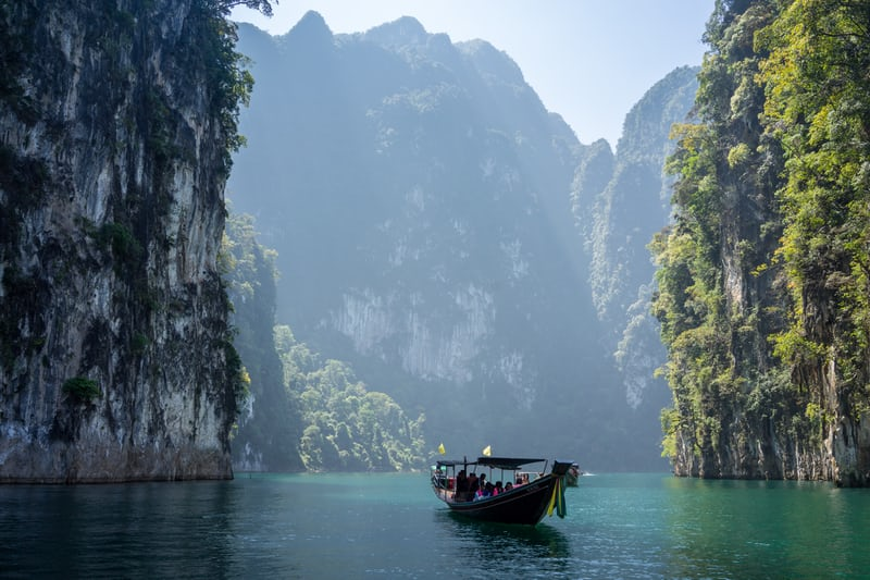 This shows a Sampan on water at bottom of mountains made of rock, one of the best places to retire in the world