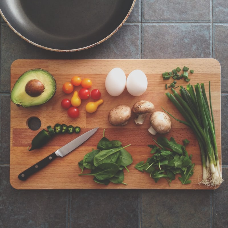 chopping board with knife, avocado, small tomatoes, spinach, spring onion, mushrooms, eggs, green chilli, frypan on bench