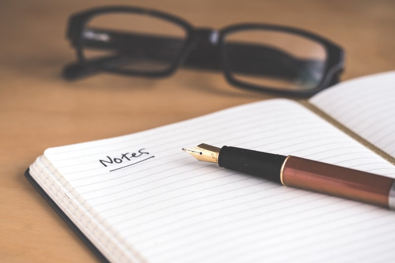 Black spectacles in background on wooden desk with brown fountain pen on notebook.