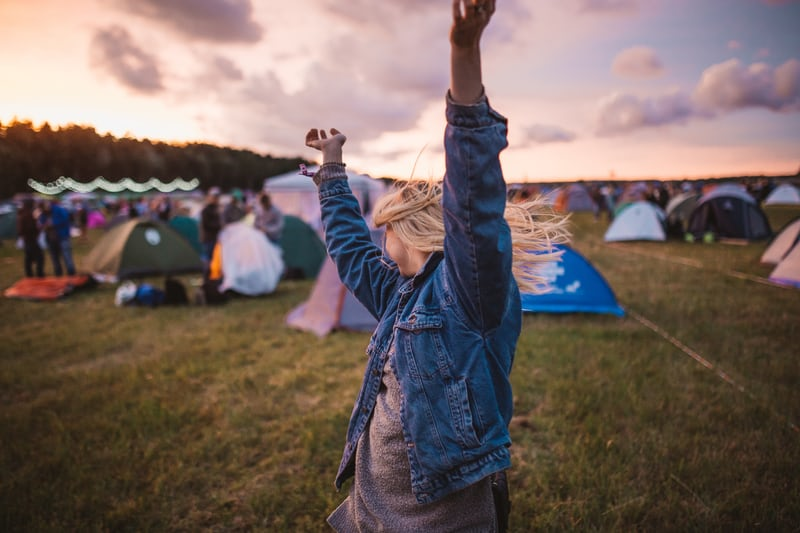 Lady dancing outside at a music campsite