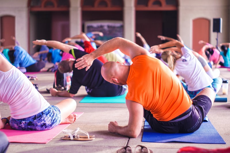 Yoga class of older people sitting on yoga mats with colourful t-shirts on.