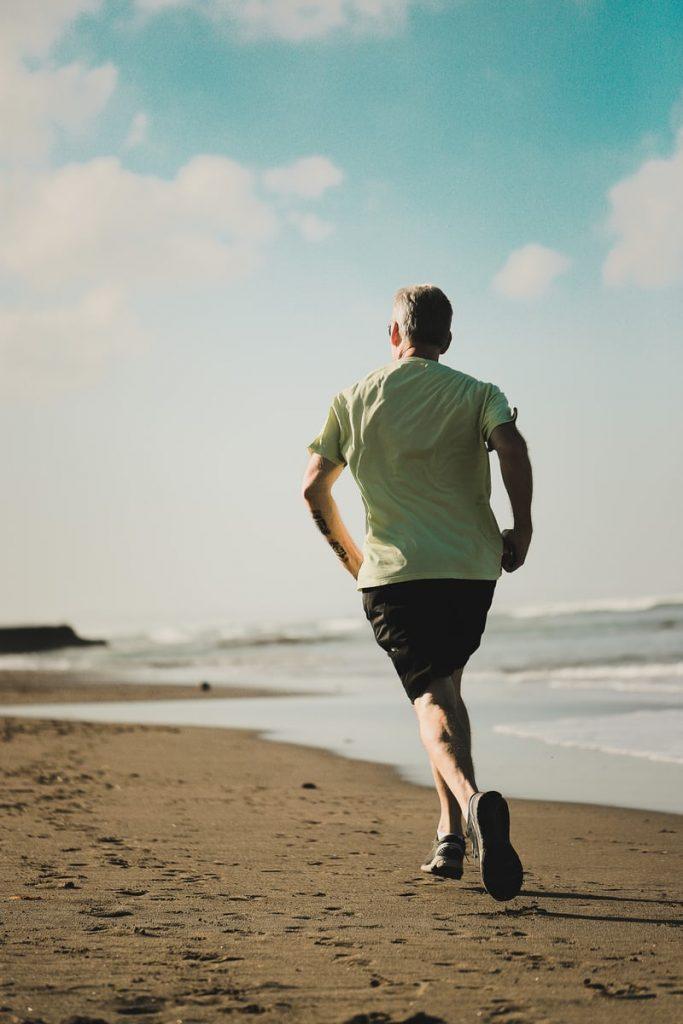 Man in black shorts, light green t-shirt running along a beach away from the camera
