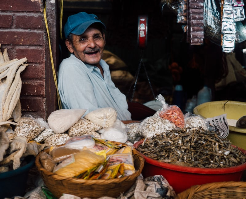 Older man sitting back laughing with fish in baskets to sell.
