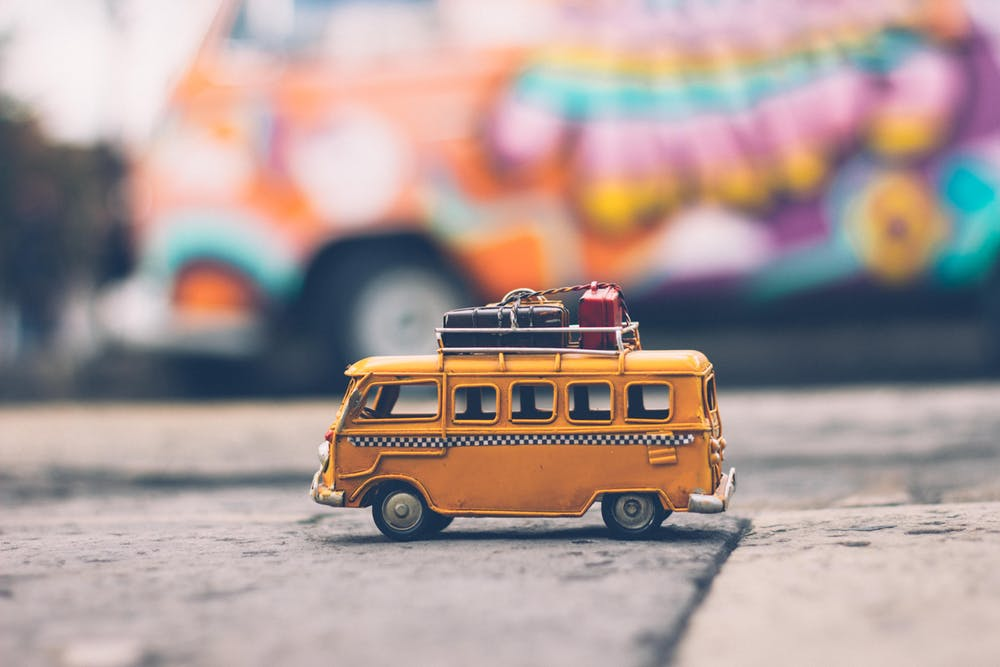 Shows a small model yellow camper van with suitcases on the top