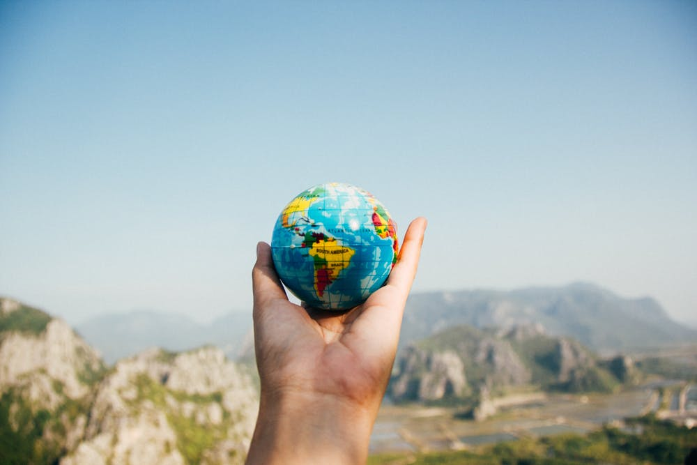 Person's hand holding small globe of world with mountains in background