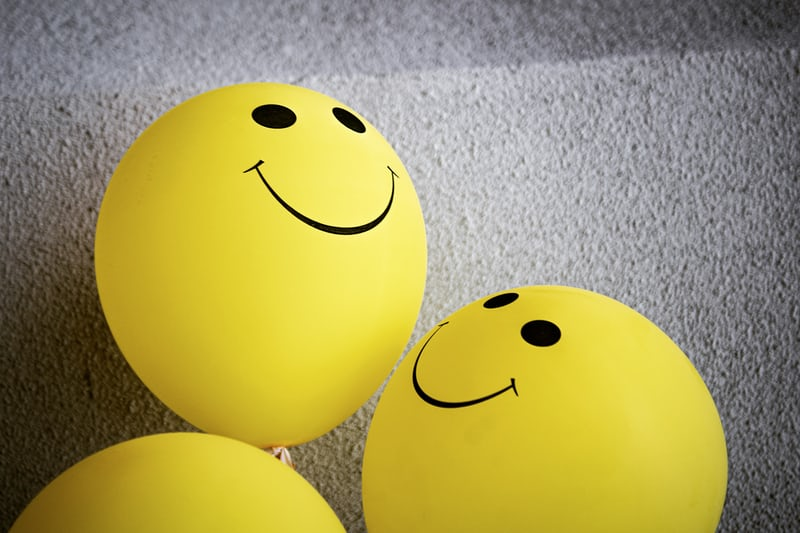 Three yellow balloons with smiley faces painted on them. 5 Characteristics Of Optimists