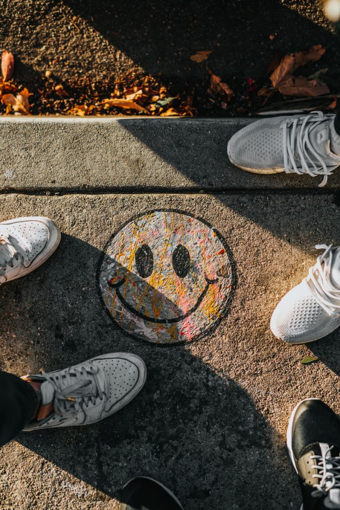 Looking down at two sets of white sneakers either side of a smiley face painted on concrete. 5 Characteristics Of Optimists
