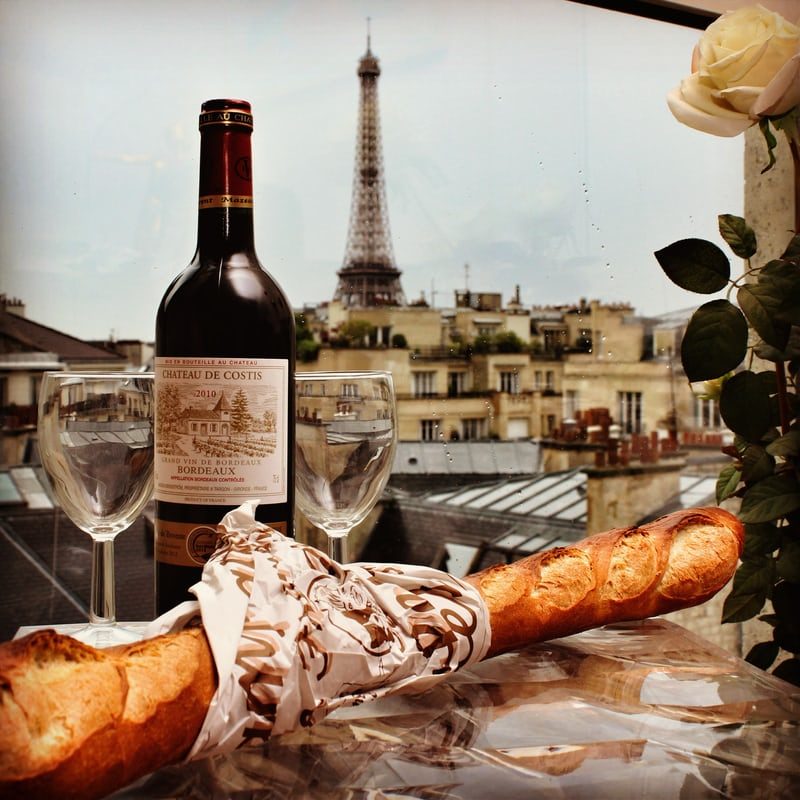 Bottle of red win=e, glasses, baguette with Eiffel Tower in the background, What's It Like To Retire To Southern France?