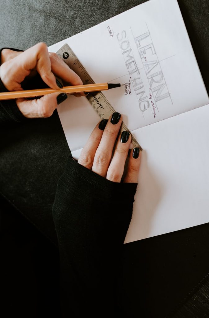 Person with black fingernail polish using a metal ruler and pencil to write Learn Something on a blank page
