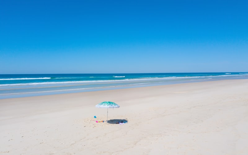 White sand beach with waves breaking in background, light blue and white umbrella on sand, halfback retirees (and others)