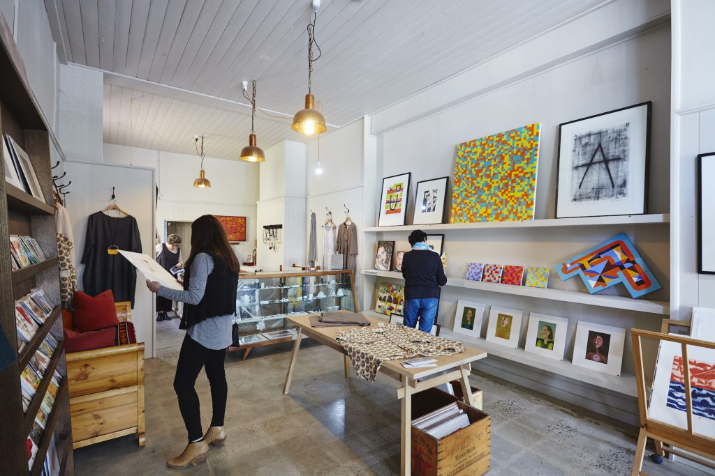 art gallery with paintings and a mane wearing a black jumper and denim jeans and a lady in black leggings, grey top holding a painting.