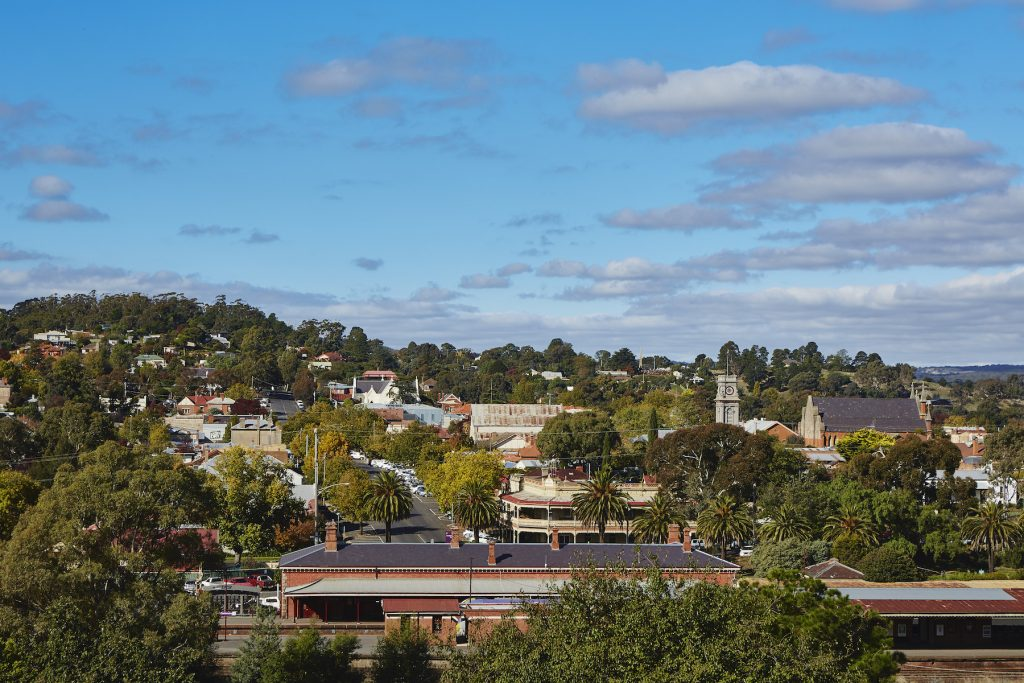 Scene of trees and buildings, a train station looking up a hll in Castlemaine.