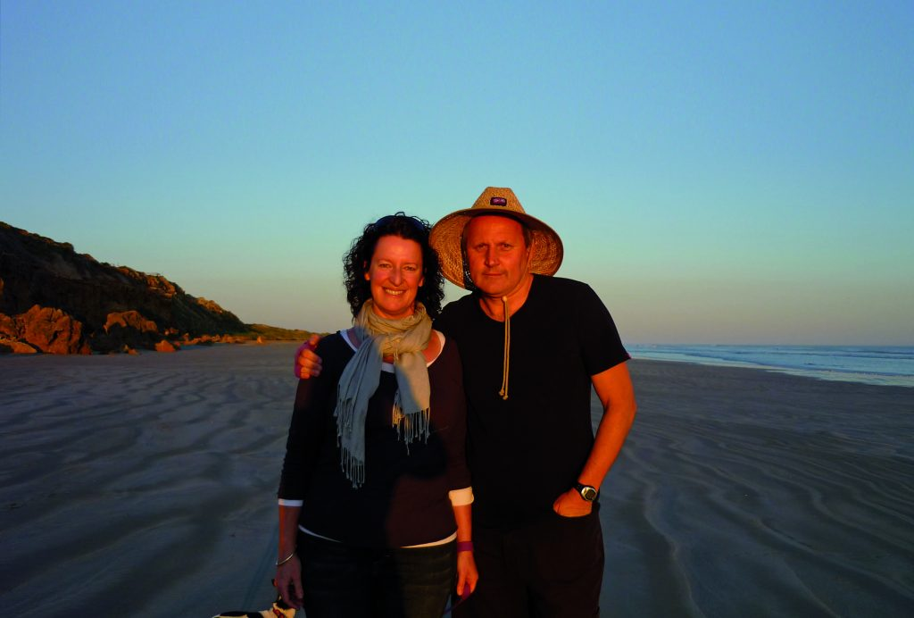 Lady and man standing on beach at sunset with man wearing a large straw hat.